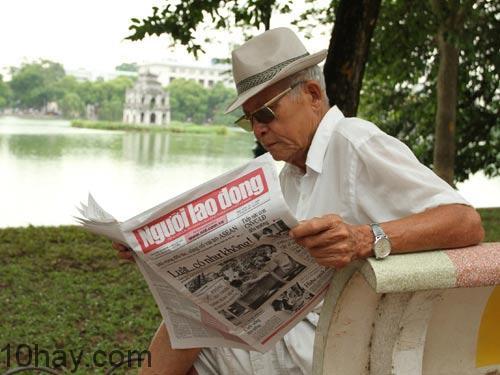 Một ông cụ đọc báo Người lao động bên hồ Gươm